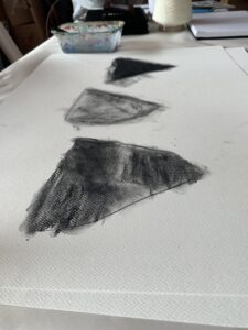 A drawing by Charlie Stephens in charcoal, with three distinct forms in varying shades of light and dark