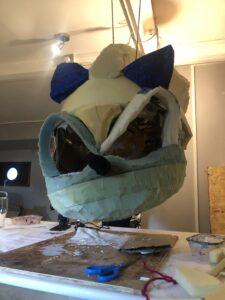 Lucy's Sonic head hangs suspended from a beam; the foam structure has now had blue velvet ears added to it