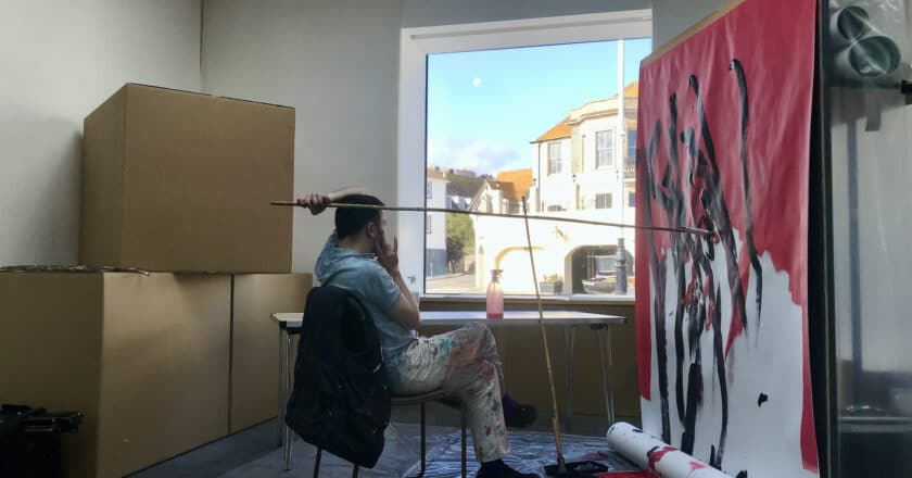 A man sat in a gallery painting onto a canvas